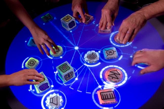 Spelers van het spel Reactables moeten fiches en pionnen verplaatsen die onderlinge relaties hebben. Deze worden aangegeven op het blauwe onderscherm.